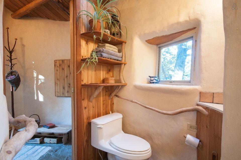 casita hecha a mano con materiales naturales locales. baño