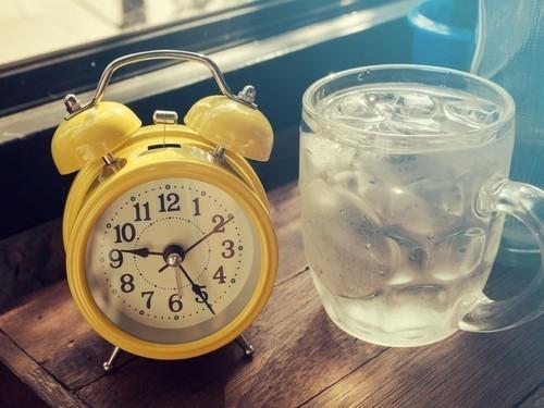 vaso de agua junto a la cama despertador